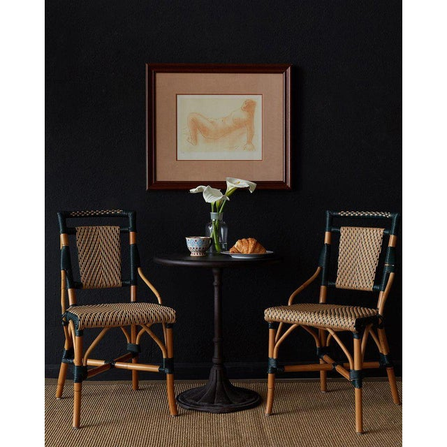Delightful pair of bamboo rattan French style bistro cafe chairs produced by Palecek. Authentic steam bent rattan frames...