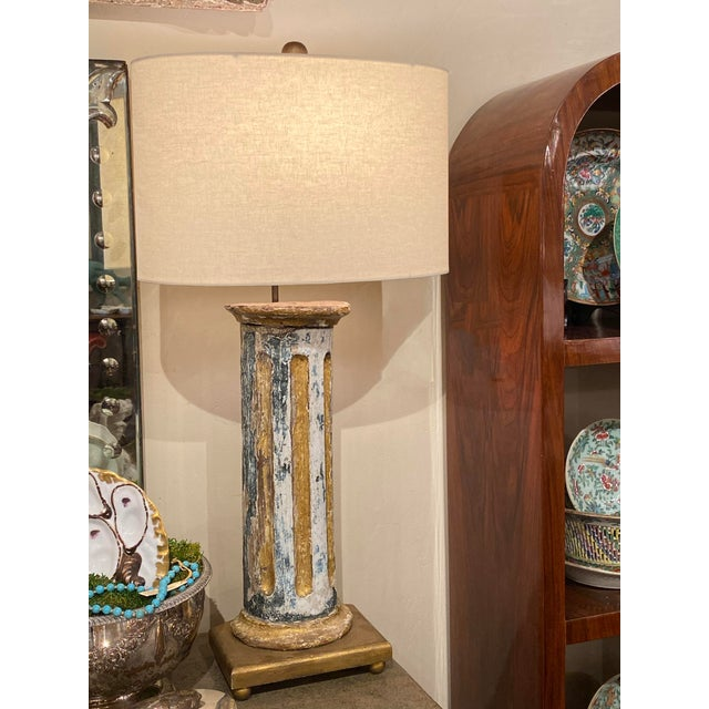 Lamp from and antique Italian column with rich blue, soothing white and decant gold paint. Sitting on a footed, square...