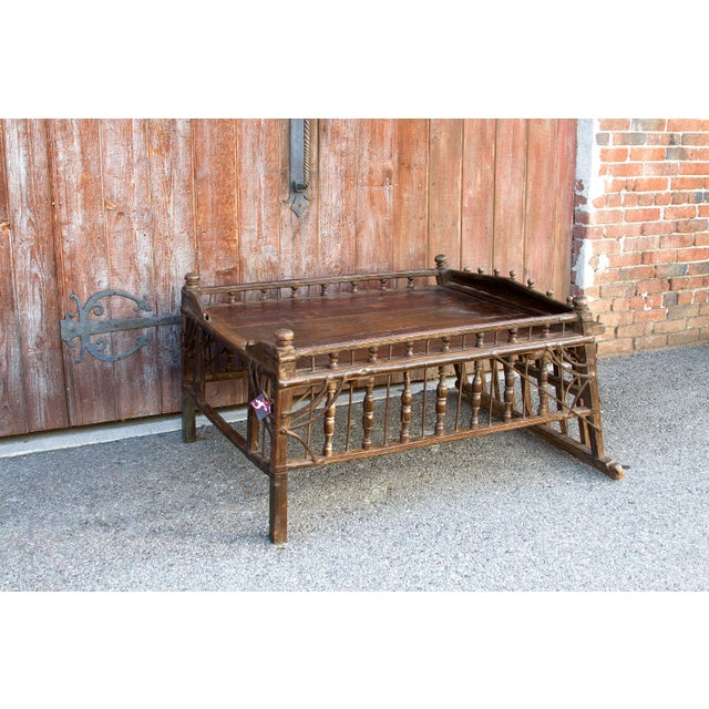 This rare antique Jhoola Coffee Table features splendid hand-carved spindle rails on three sides and a beautiful carved...