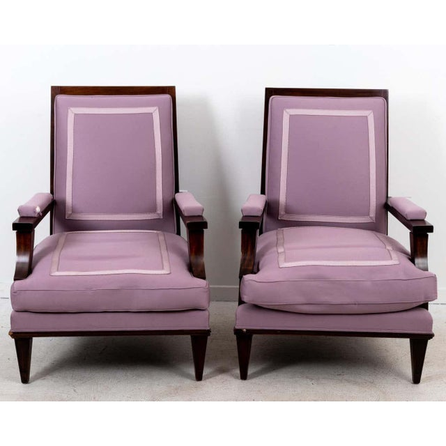 Circa 1940s pair of armchairs in the style of Jules Leleu with polished Walnut frames, square shaped backs, and lilac...