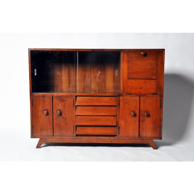 This British colonial modern bar cabinet is from Mandalay and is made from teak wood. It features sliding glass doors and...