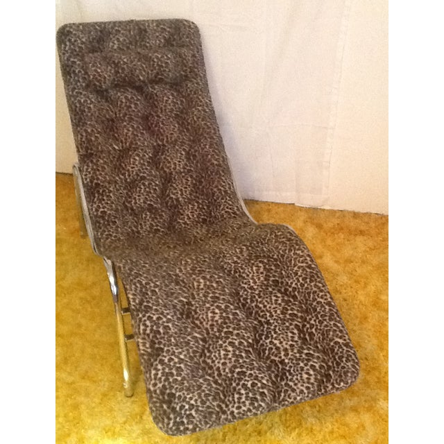 Leopard and chrome wave/chaise lounge. Has chrome frame and leopard cover with black backing. There is a pillow attached...