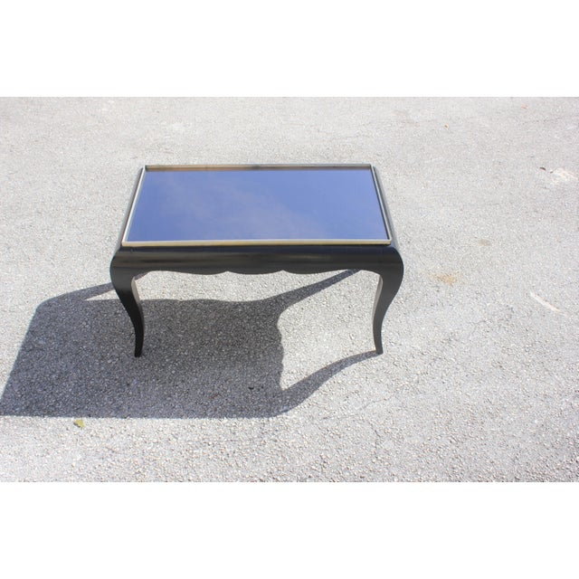 Beautiful French Art Deco Jules Leleu style ebonized period side table or coffee table, mirror top circa 1940s. The table...