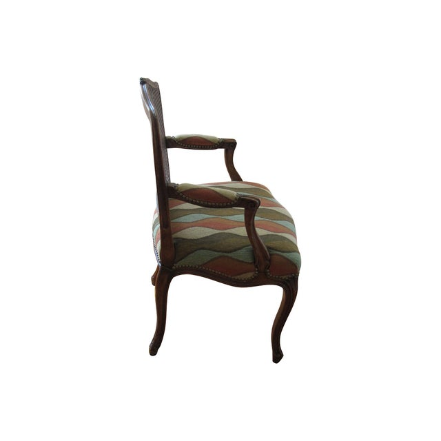 Carved walnut continental (possibly Italian) Louis-style armchair with groovy later colorful fabric and cane back. Seat...