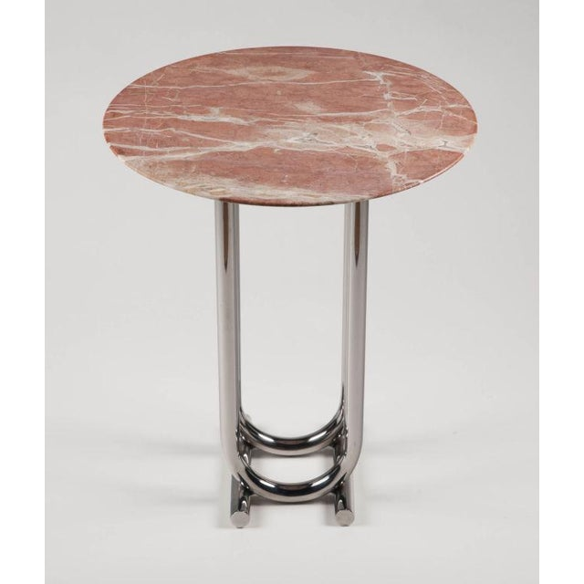 A Deco influenced occasional table with a white veined rose marble circular top raised on a bent tubular brushed steel...