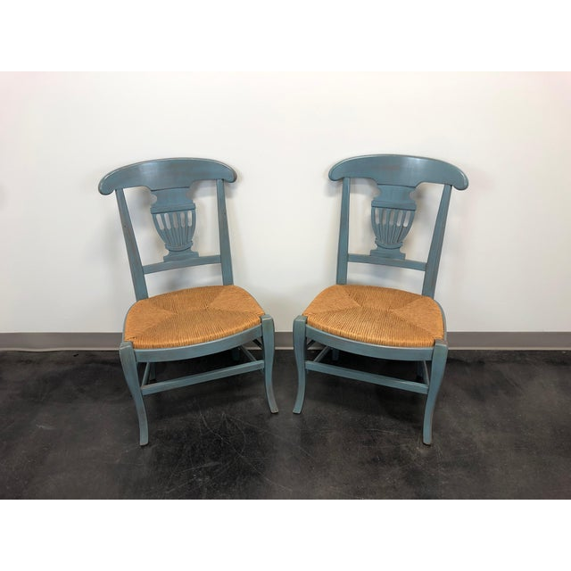A pair of cottage style dining side chairs with a powder blue distressed finish and rush seats. Unbranded but very high...