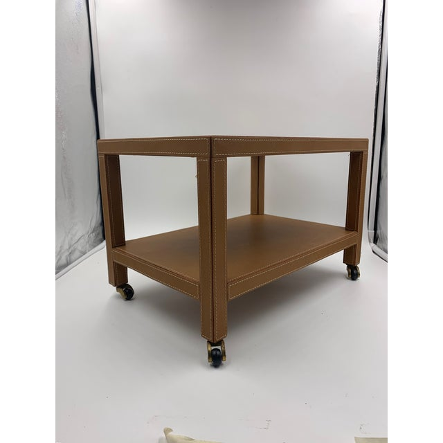 A Dimuntive two tier camel leather trolley with top stitching on brass casters. There is not a label and the maker is...