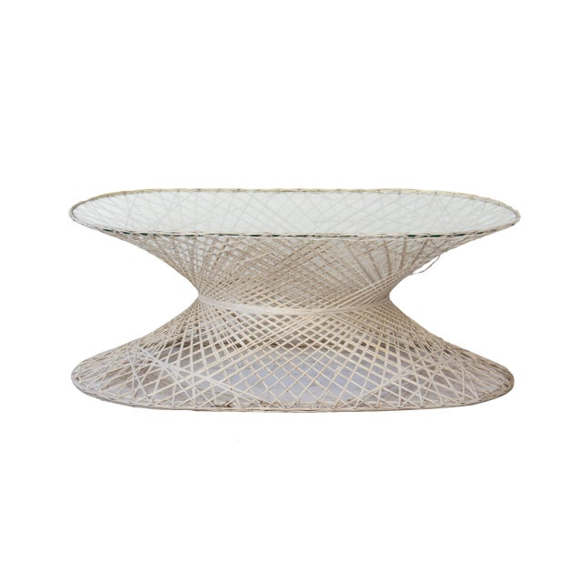 Spun fiberglass coffee table by Woodard. Off white color, open and light in feel but sturdy. Hourglass shape with an long...