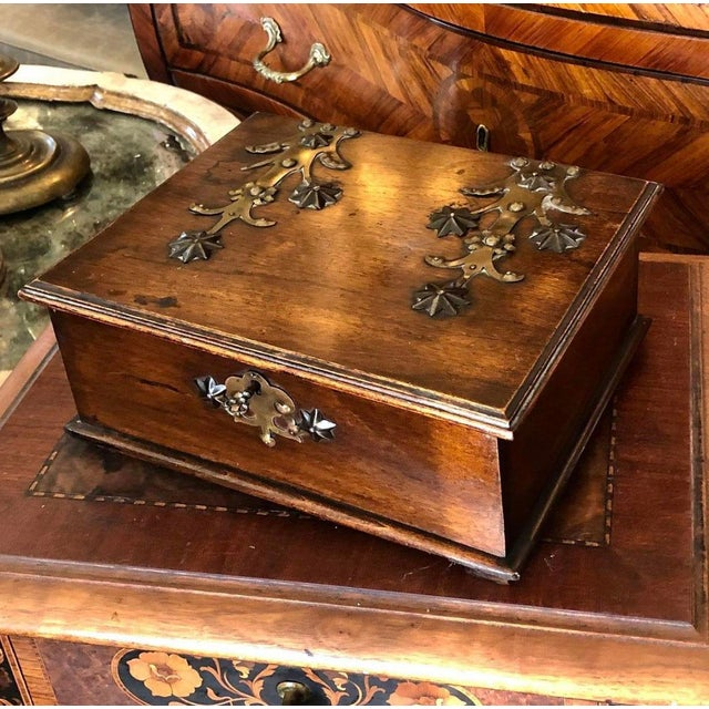 Turn of the century German walnut box with brass decoration on the top of the box and the bottom. Original key.