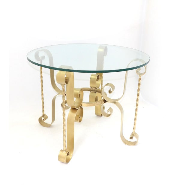1960's wrought iron round glass end table. Iron was recently refreshed with a coat of gold paint. The glass is in...