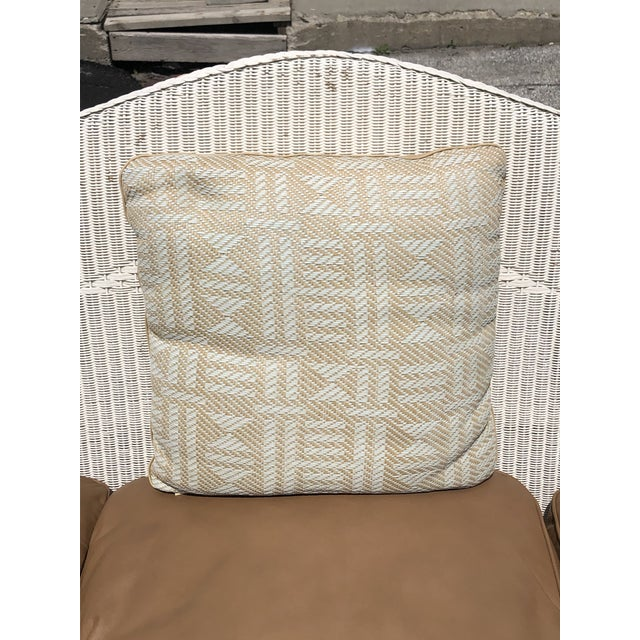 White wicker sofa with leather cushions and two Hermès pillows. Hermes pillows are evenly faded and have really soft...
