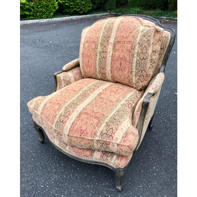 Stylish and comfortable French bergere style chair with limed wood look finish. Handsomely upholstered in a paisley...