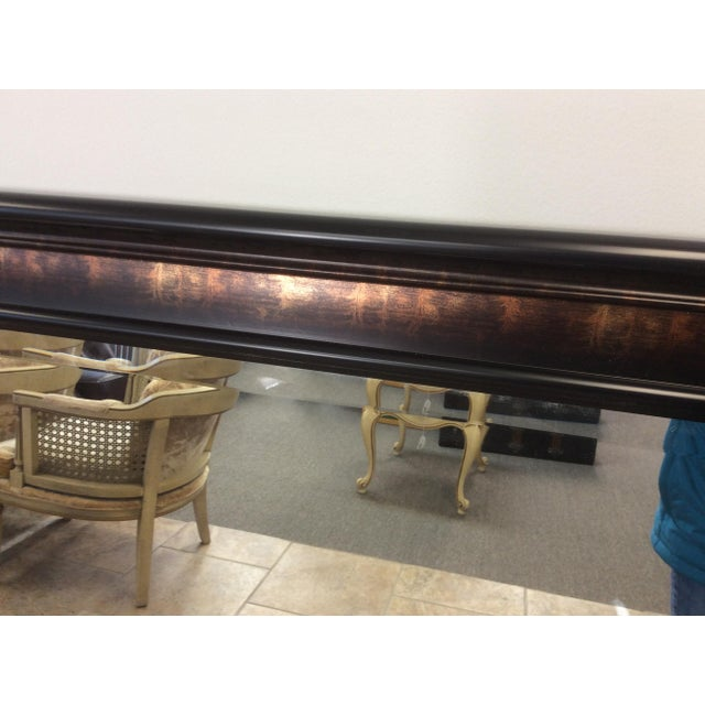 This is a very large mirror for a wall or above a fireplace. The outside rim of the frame is black. Then it goes to an...