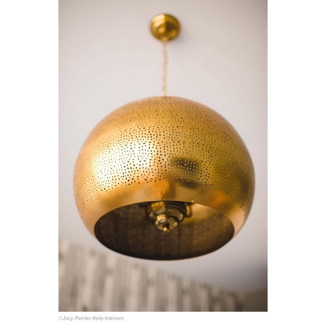 Handcrafted with a brilliant natural brass finish and an organic perforated design this pierced metal sphere pendant is...