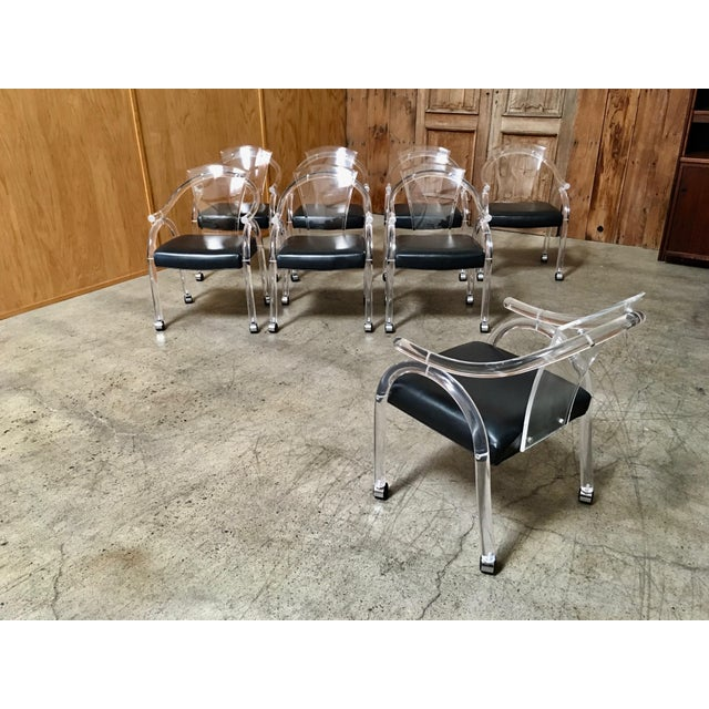 Vintage acrylic dining chairs on casters with black textured vinyl seats. These can also be used as office seats.