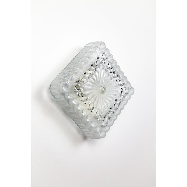 A fabulous, frosted and clear, molded glass sconce with circular designs trimming its square shape. It looks great...