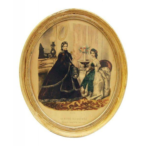 A beautifully framed antique print of two Victorian ladies in full dress sitting in a parlor. It is framed in its original...