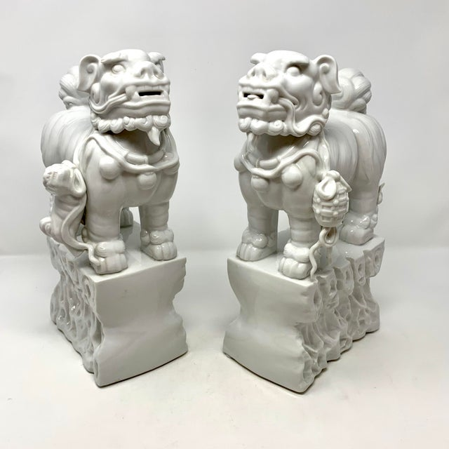 Pair of 1960s Blanc de Chine Italian porcelain Chinese foo dog statues. Very finely executed, the dogs are slightly...
