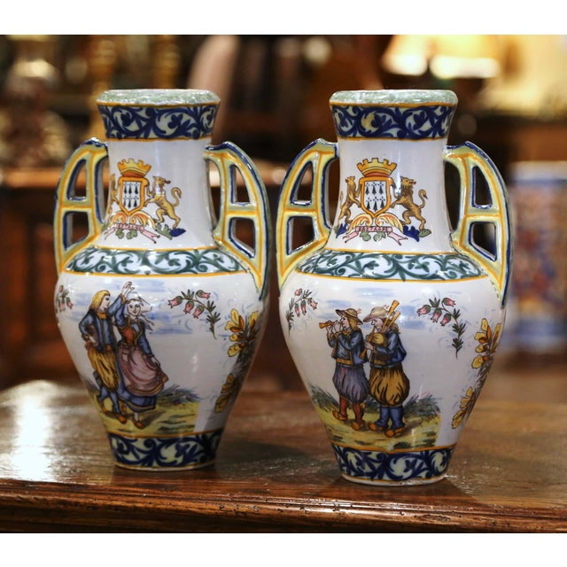 Decorate a mantel or table with this colorful pair of antique faience vases. Crafted in Brittany, France, circa 1890, both...