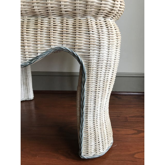 This wicker side table has a white-washed finish and is trimmed in blue-gray along the top of the table and the legs.
