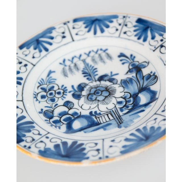 Lovely antique 18th-Century Dutch Delft hand painted floral plate in vibrant cobalt blue and white with a yellow gold rim....
