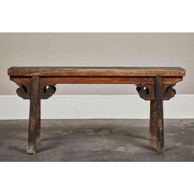 Petite Chinese wooden bench with heavily patinated finish. Evenly worn with age. Works as occasional seating, or tucked...