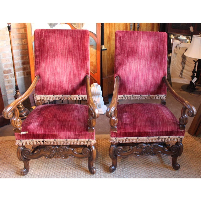 Circa 1920 walnut armchairs with original red velvet covers. Some wear to fabric.