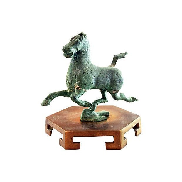 Statuette of a galloping horse displayed on an Asian-style brass riser. Horse has opening at base and top of head. Riser...