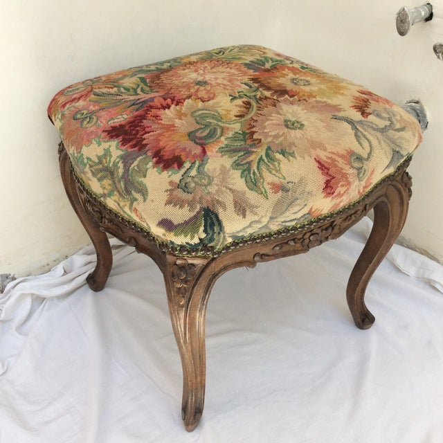 Offered is a beautiful antique carved walnut stool with antique tapestry textile upholstery.