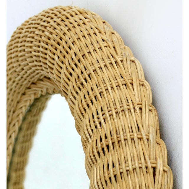 Offered for sale is an over-scale vintage elongated oval woven wicker mirror. The wicker is natural in color and in...