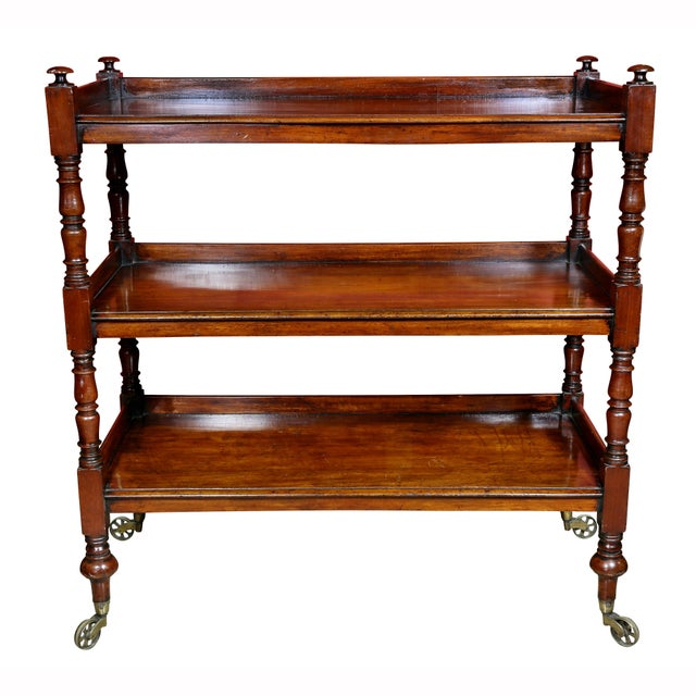 Book trolley with three shelves with turned supports ending on toupie feet with large casters.