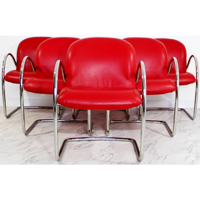 For your consideration is a brilliant set of six, red leather and chrome, dining chairs with arms by Brueton. In excellent...