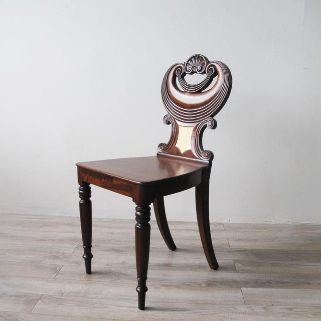 English Regency Mahogany Hall Chair with stylized swag backrest and shell crestrail, later maple crest inlay, Early 19th...