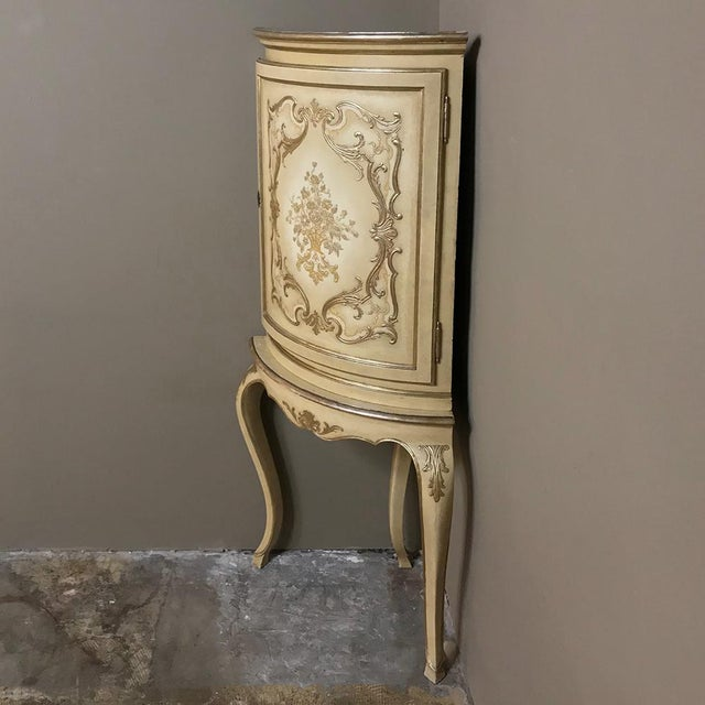 Antique Italian Baroque Painted Corner Cabinet features a bowed facade carved and hand-painted to perfection on a neutral...