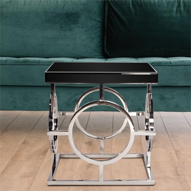 This Side Table features a stainless steel bar frame detailed with a circular design on each side. It is topped by a black...
