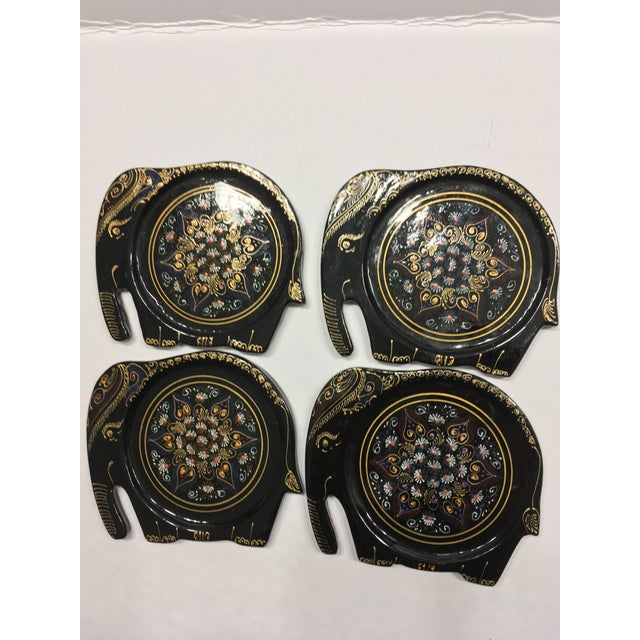 A set of four coasters hand made in India. Each coaster is hand cut, shaped as an elephant and lacquered with black glossy...