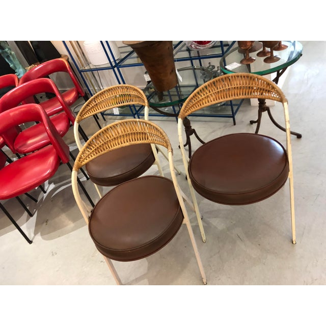 A rare trio of Arthur Umanoff for Shaver Howard painted wrought iron, rattan, and leatherette dining chairs in original...