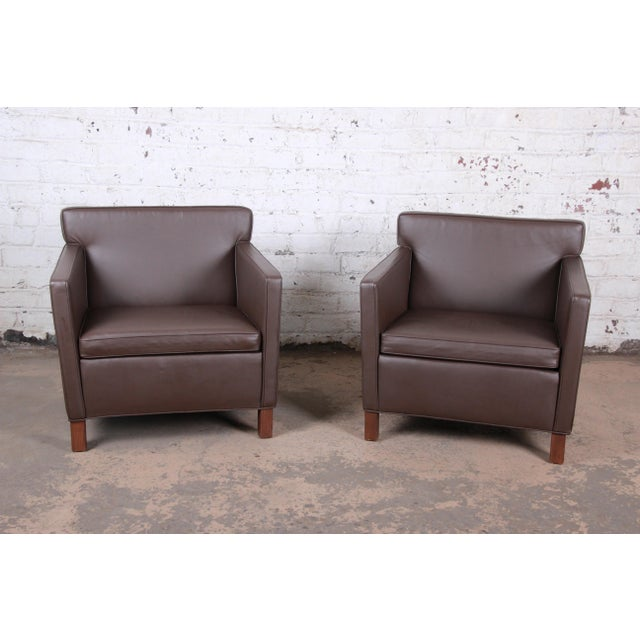 An exceptional pair of brown leather lounge chairs designed in 1927 by Ludwig Mies Van Der Rohe and produced by Knoll...