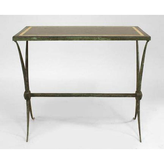 French Art Deco green patinated bronze end table with inset rectangular black marble top above tapering X legs joined by a...