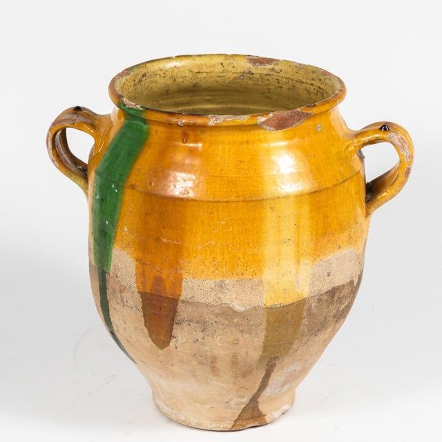 A yellow glazed confit pot with green markings and handles. Originating in France, circa 1890.