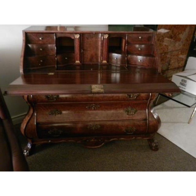 Late 18th century Dutch drop front desk in walnut and burl walnut featuring a bombe shaped body with three drawers, carved...