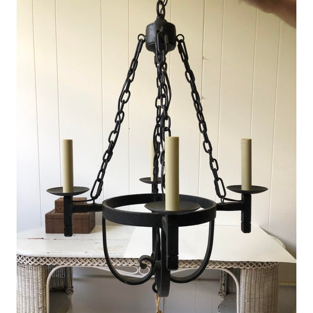 This 20th Century chandelier is made of black iron in the Spanish or Mediterranean style. It has a decorative ceiling...
