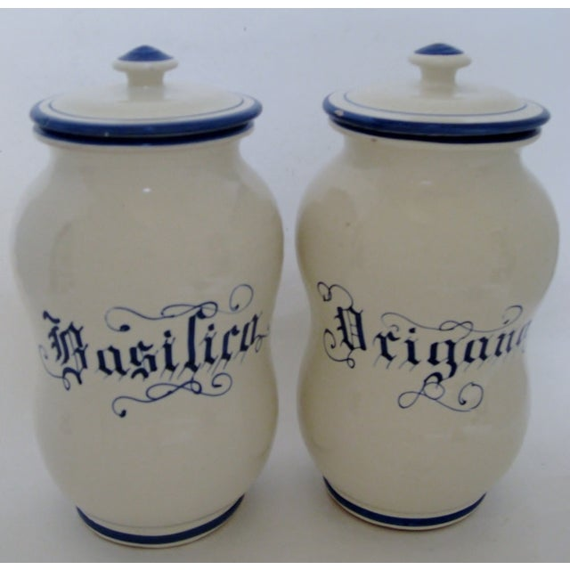 Tall rustic Italian ceramic canisters in ivory glaze with basil and oregano in blue calligraphy script. Lids have a few...