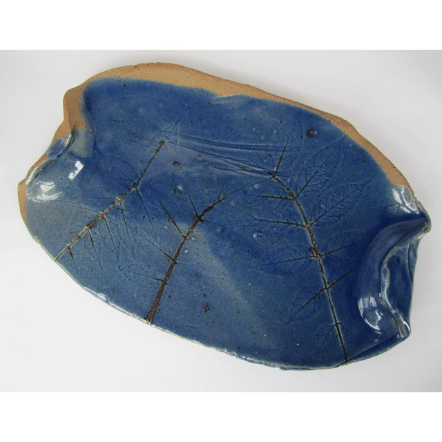 Beautiful cobalt blue handmade pottery platter with folded handles and pressed leaf details. A great piece for your next...