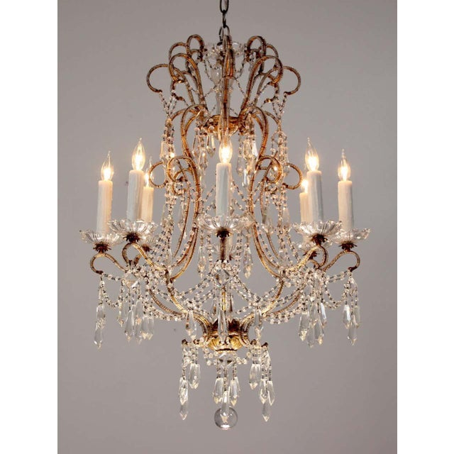 Gorgeous, 1940s Italian beaded chandelier featuring an elegantly scrolled gilt-iron frame which has been hand-beaded...