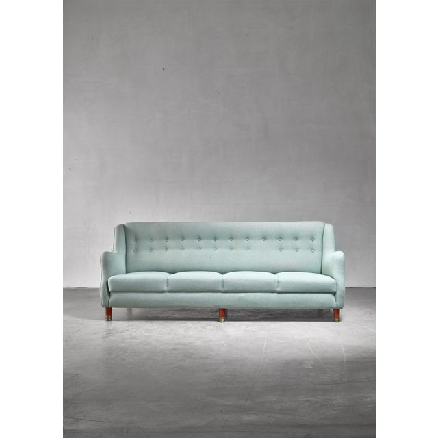 A model GJ180 four-seater sofa by Grete Jalk for Johannes Hansen. The sofa has a light green wool upholstery and stands on...