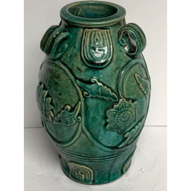 Chinese green glazed lotus motif vase, with three handles.
