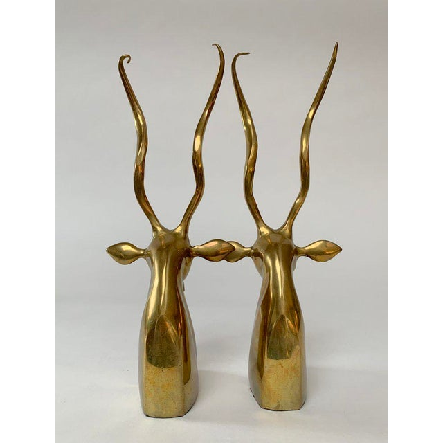 Pair of weighted brass gazelle busts with long curling antlers are almost too chic to be used as utilitarian bookends....