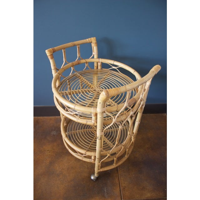 "Unique vintage round rattan bar cart featuring two circular 21""glass shelves. Dimensions: 26ʺW × 36.5ʺH"