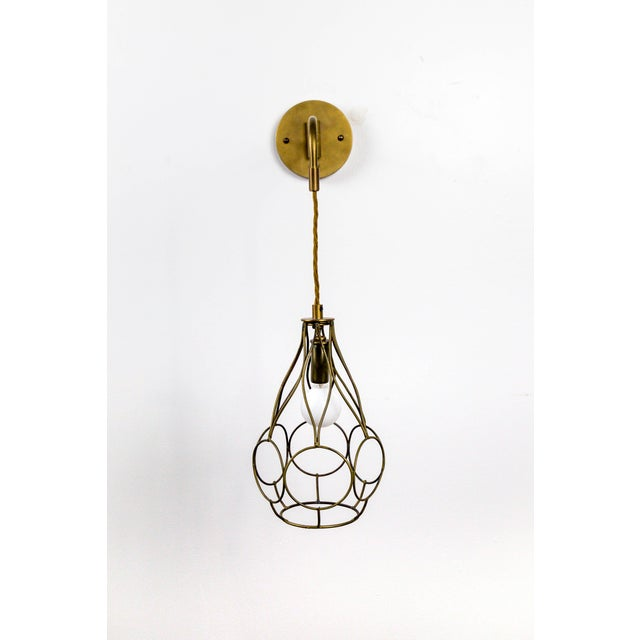 A custom made wall light with a hanging, brass, pear shaped cage with a circular design. It's long swing arm has dangling,...